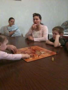 Sister Nicole Hanney (Pastor's wife and music leader) eating strawberry and playing Tsuro.